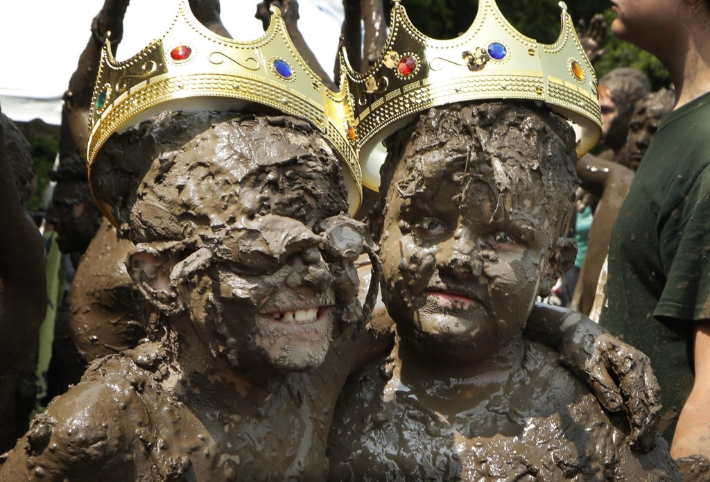 Mud Day Queen Riley Tulgetske, left, embraces Mud Day King Phoenix Crowder during Mud Day at the Nankin Mills Park, Tuesday, July 9, 2019, in Westland...