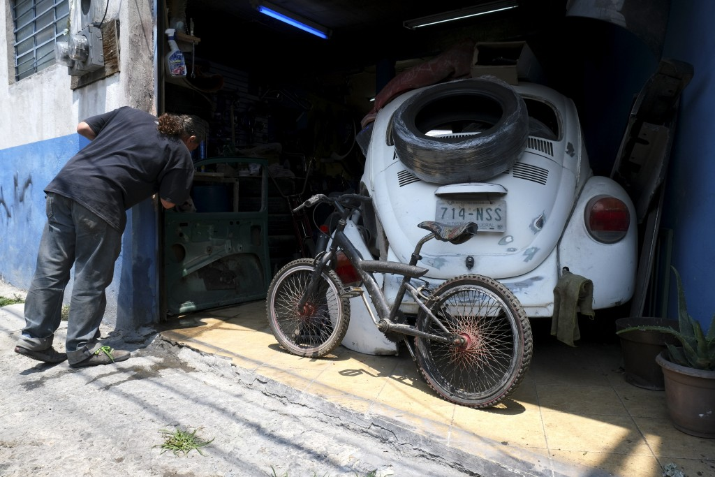 "Mechanic Juan Jose Fragoso looks inside his shop where a Volkswagen Beetle awaits repair in a neighborhood of Mexico City known colloquially as ""Vocho"