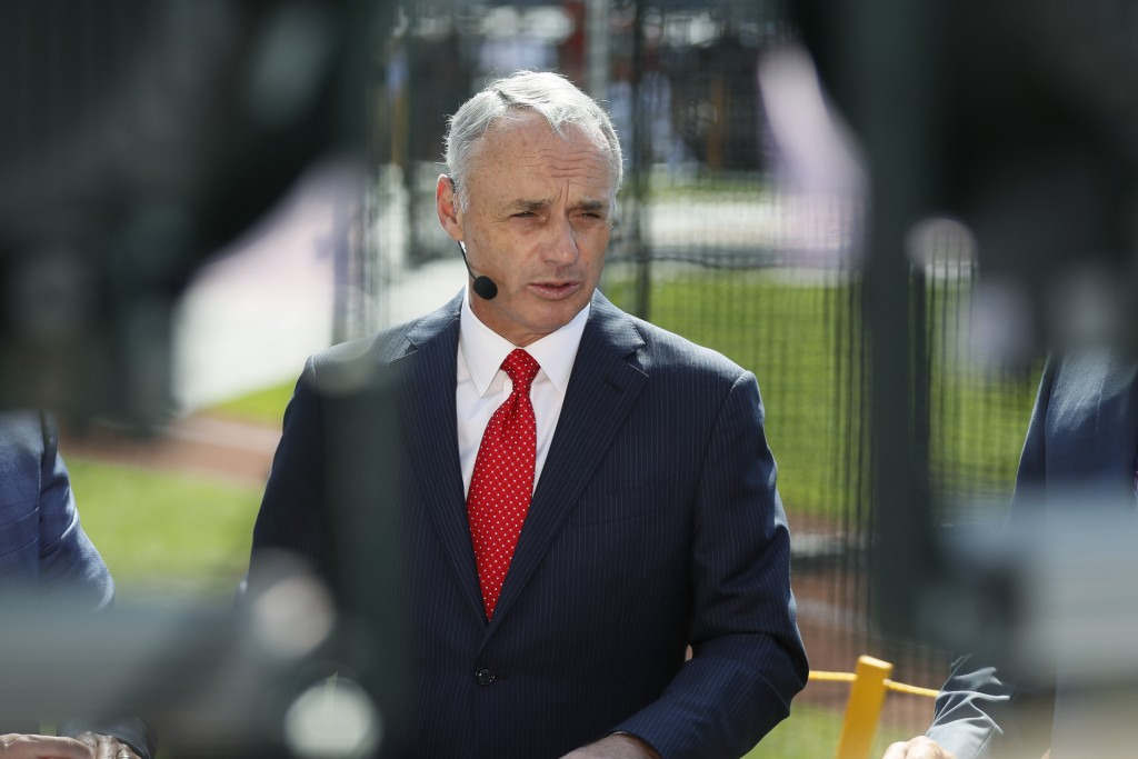 Commissioner Rob Manfred is interviewed as the American League players warm-up for the MLB baseball All-Star Game, Tuesday, July 9, 2019, in Cleveland