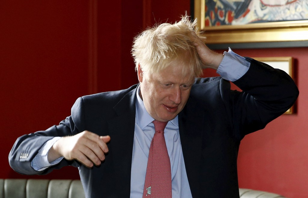 Conservative Party leadership candidate Boris Johnson gestures during a visit to Wetherspoons Metropolitan Bar in London, Wednesday July 10, 2019. (He