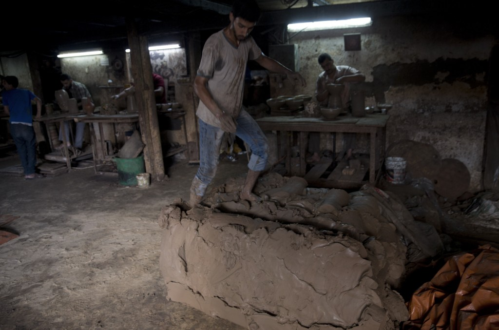 In this Saturday, July 6, 2019 photo, a Palestinian worker prepares the clay at a pottery workshop in Gaza City. Talk about old Gaza, and what pops up