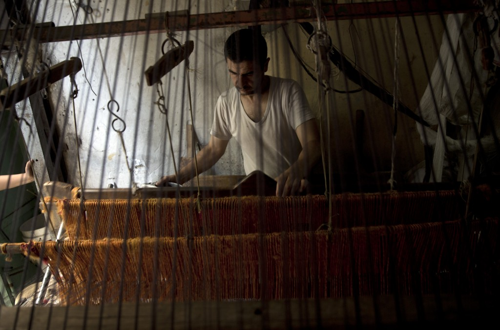 In this Saturday, July 6, 2019 photo, Palestinian worker weaves carpets on a traditional wooden loom at a carpets factory in Gaza City. Talk about old