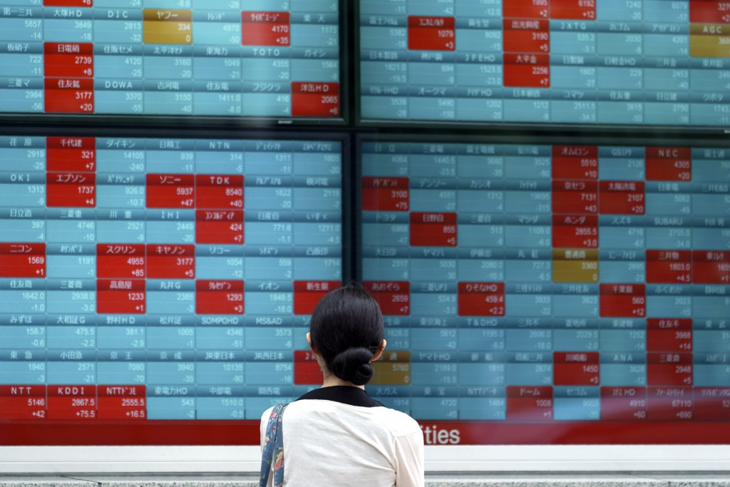 A woman looks at an electronic stock board showing Japan's Nikkei 225 index at a securities firm in Tokyo Wednesday, July 10, 2019. Asian shares were ...