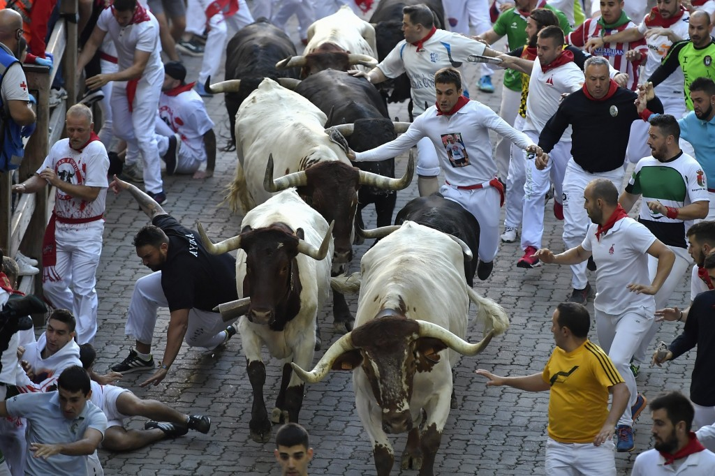 Revellers run next to fighting bulls during the running of the bulls at the San Fermin Festival, in Pamplona, northern Spain, Wednesday, July 10, 2019...