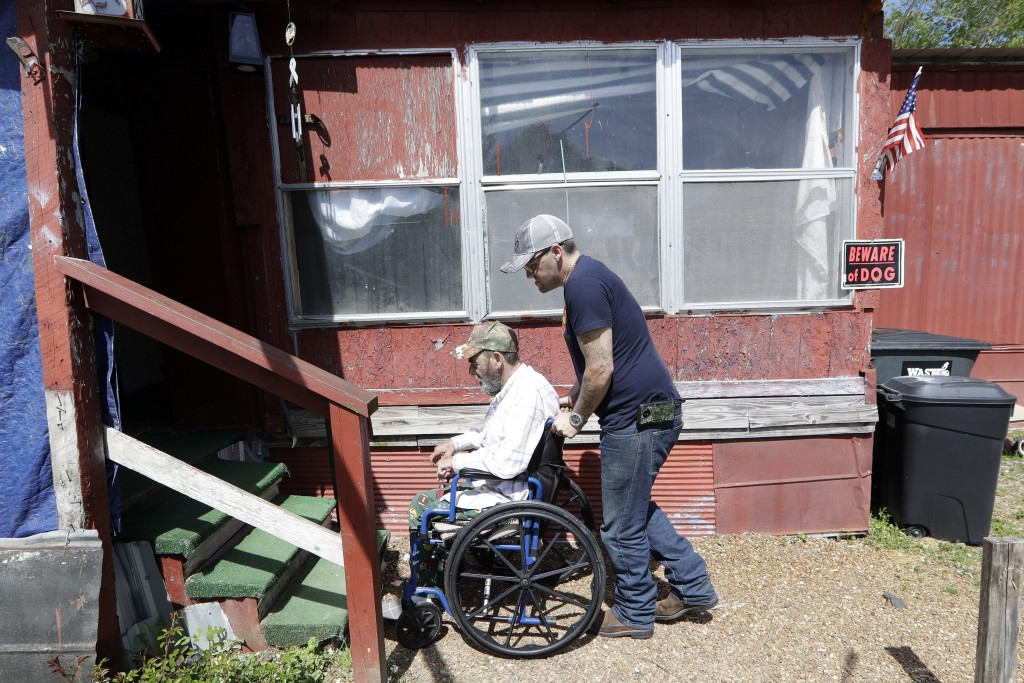 In this April 16, 2019, photo, Johnny Gibbs helps his disabled father, Mike, 65, into their home in Liberty, Tenn. Johnny Gibbs has been trying to get