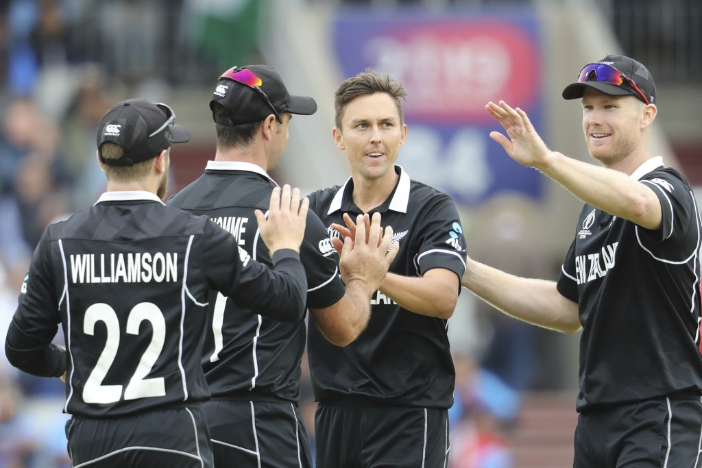 New Zealand's Trent Boult, without cap, celebrates with teammates after dismissing India's Ravindra Jadeja during the Cricket World Cup semifinal matc