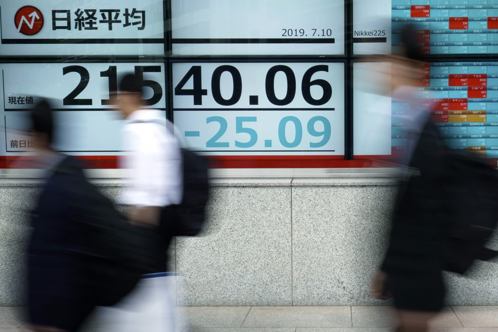 People walk past an electronic stock board showing Japan's Nikkei 225 index at a securities firm in Tokyo Wednesday, July 10, 2019. Asian shares were