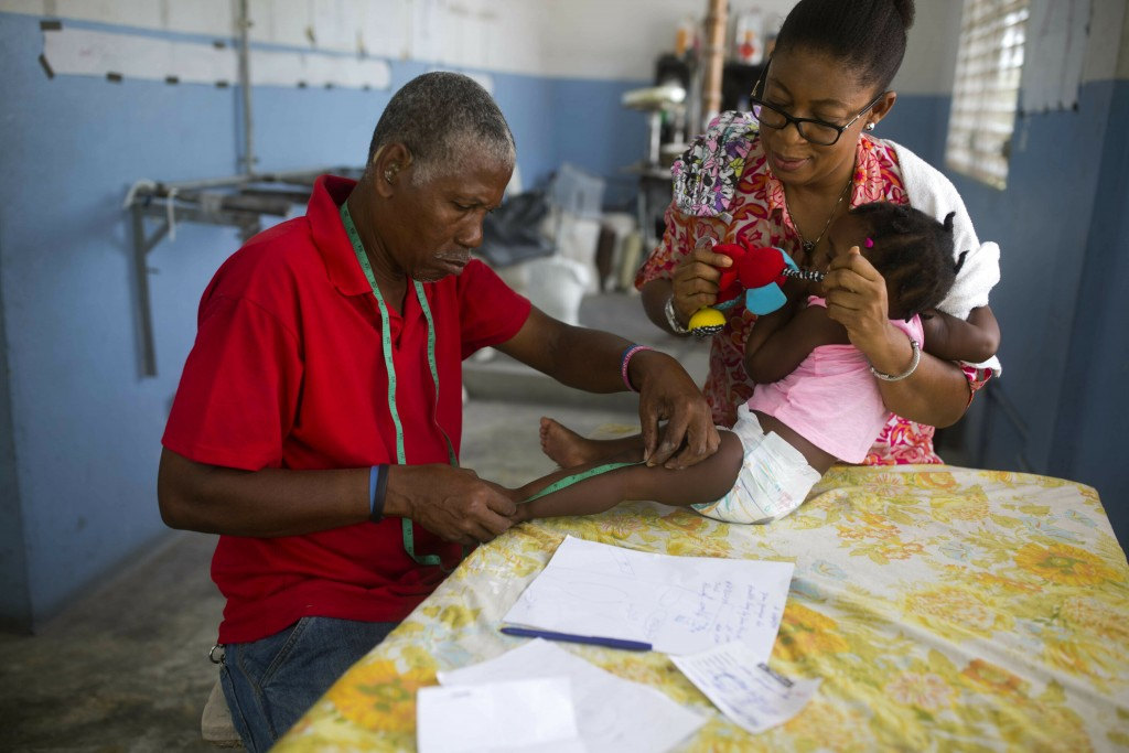 In this May 22, 2019 photo, technician Emmanuel Celicourt measures a child for an orthotic brace at the St. Vincent's Center in Port-au-Prince, Haiti....