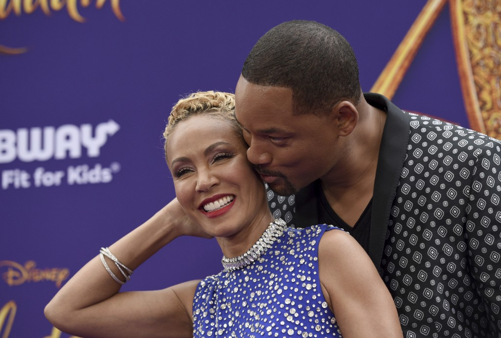"""FILE - In this May 21, 2019 file photo, Will Smith, right, kisses Jada Pinkett Smith as they arrive at the premiere of """"Aladdin"""" at the El Capitan The"""