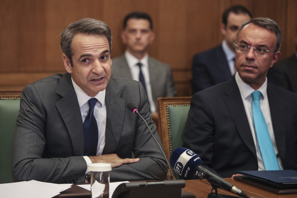 Greek Prime Ministers Kyriakos Mitsotakis, left, speaks next to Finance Minister Christos Staikouras, as new government participate in a first cabinet