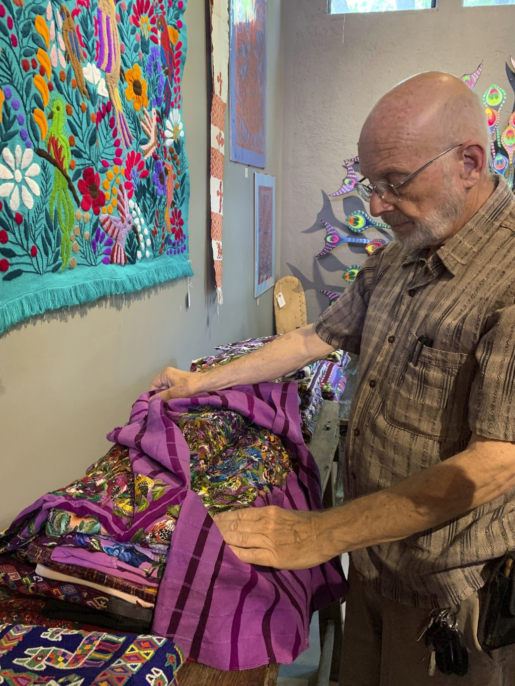 This June 17, 2019 photo shows gallery owner Mayer Shacter holding a hand-embroidered Guatemalan garment, at Galeria Atotonilco near San Miguel de All