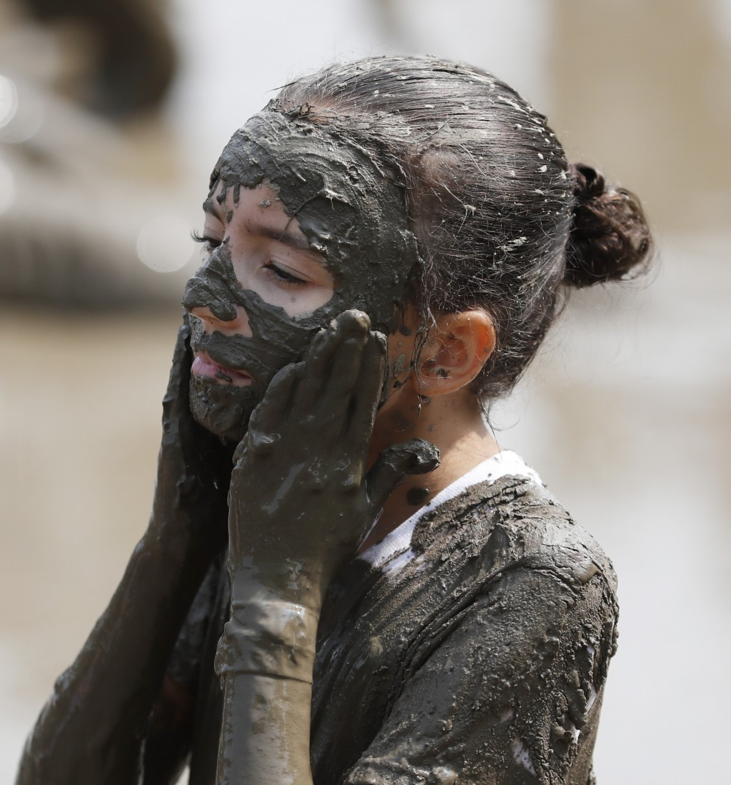Tmiamelia Harris, 11, applies mud to her face during Mud Day at the Nankin Mills Park, Tuesday, July 9, 2019, in Westland, Mich. The annual day is for