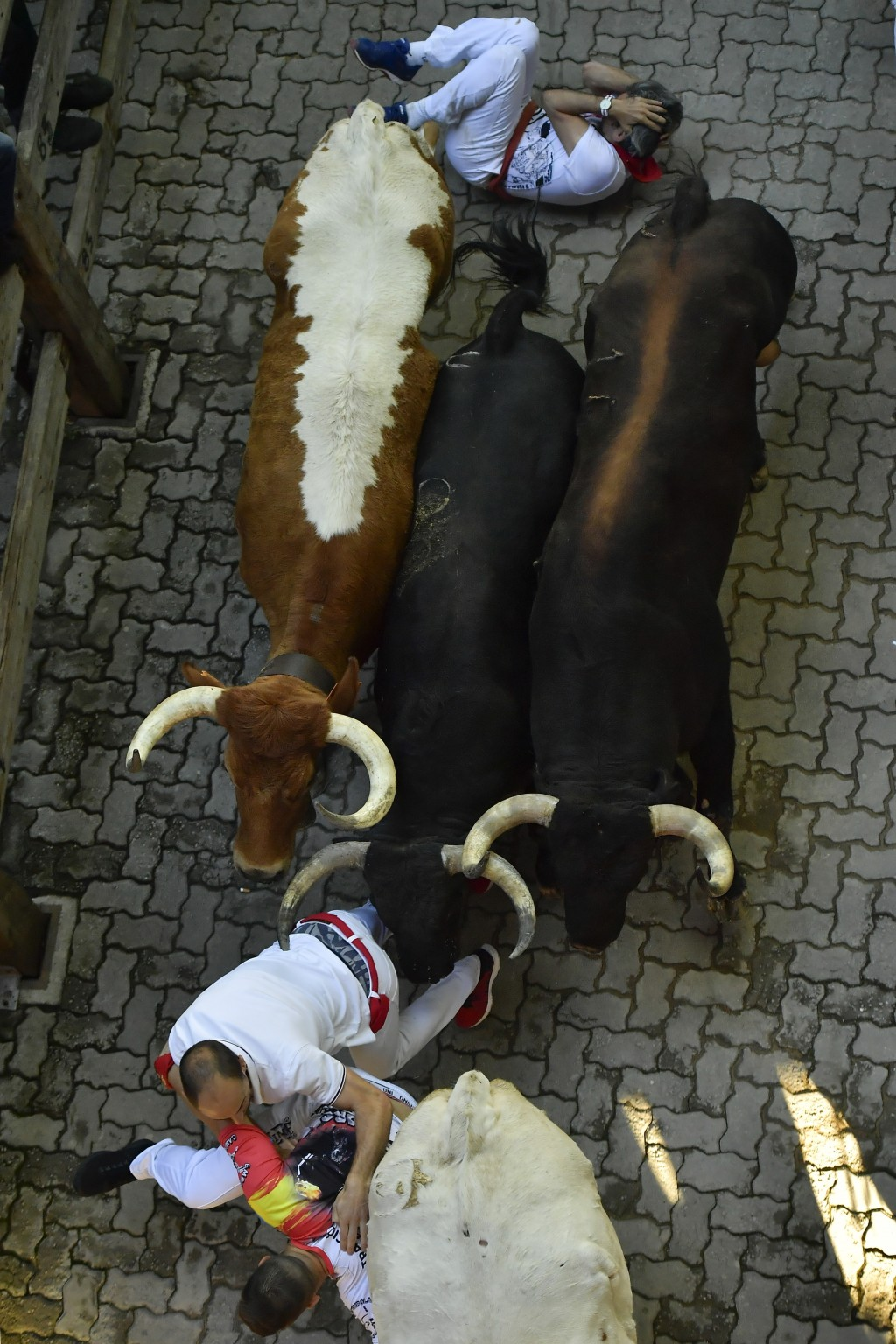 Revellers fall down during the running of the bulls at the San Fermin Festival, in Pamplona, northern Spain, Wednesday, July 10, 2019. Revellers from ...