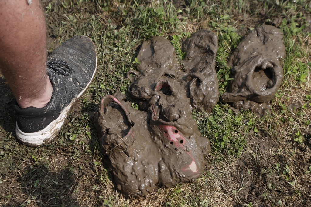 Mud covered shoes are seen on the sidelines during Mud Day at the Nankin Mills Park, Tuesday, July 9, 2019, in Westland, Mich. The annual day is for k