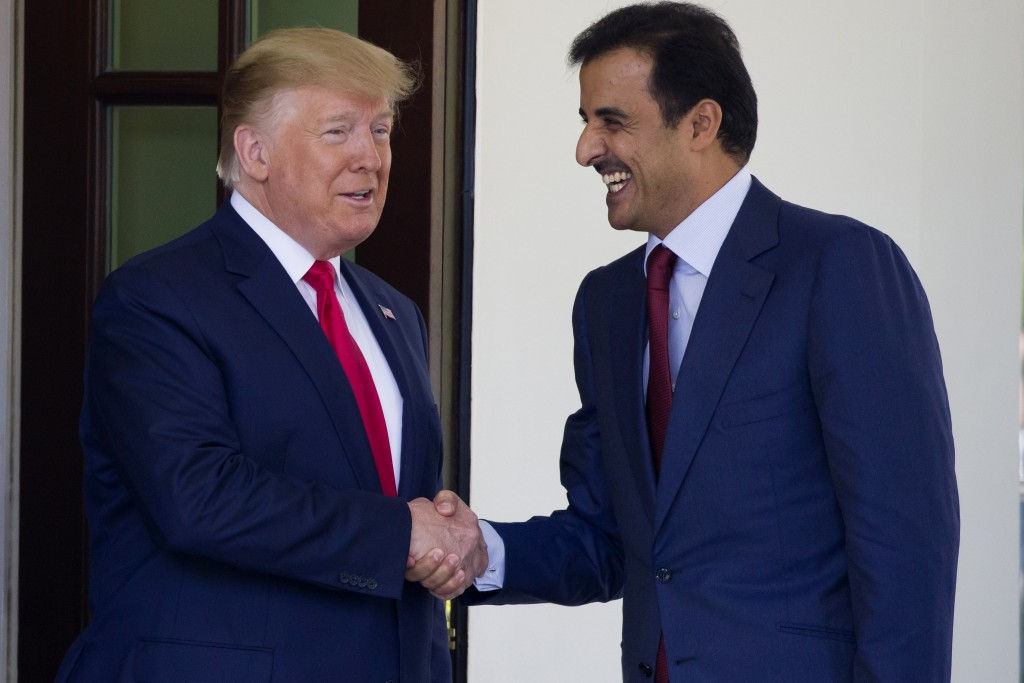 President Donald Trump shakes hands as he welcomes Qatar's Emir Sheikh Tamim bin Hamad Al Thani upon his arrival at the White House, Tuesday, July 9,