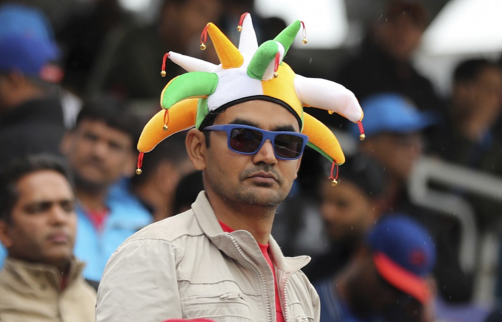 An Indian fan awaits before the Cricket World Cup semi-final match between India and New Zealand was suspended for the day due to rains at Old Traffor