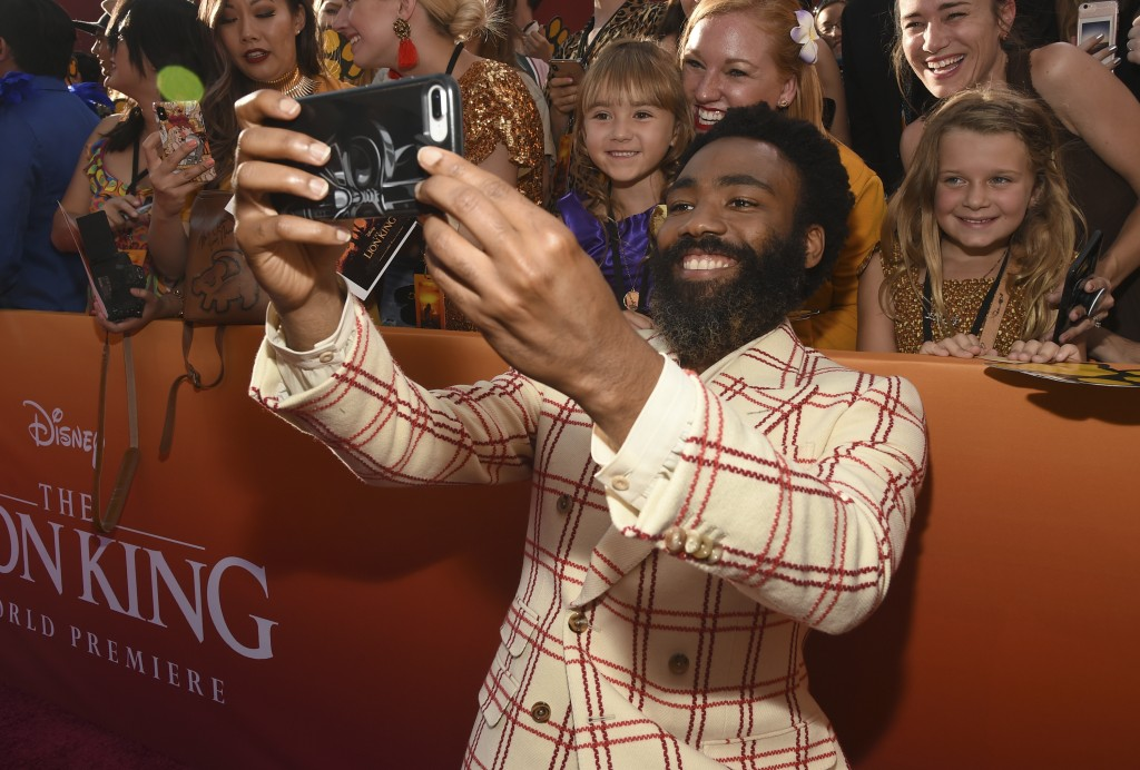 Donald Glover takes a selfie with fans as he arriv...