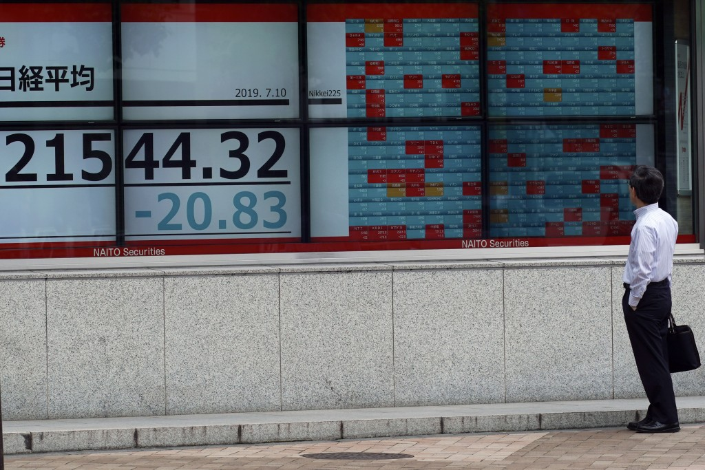 A man looks at an electronic stock board showing Japan's Nikkei 225 index at a securities firm in Tokyo Wednesday, July 10, 2019. Asian shares were mo...