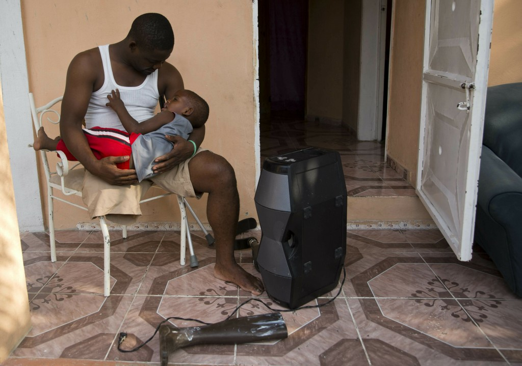 In this June 5, 2019 photo, prosthetic technician Wilfrid Macena cradles his son Wilensky while sitting on their front porch in Carrefour, Haiti. Mace
