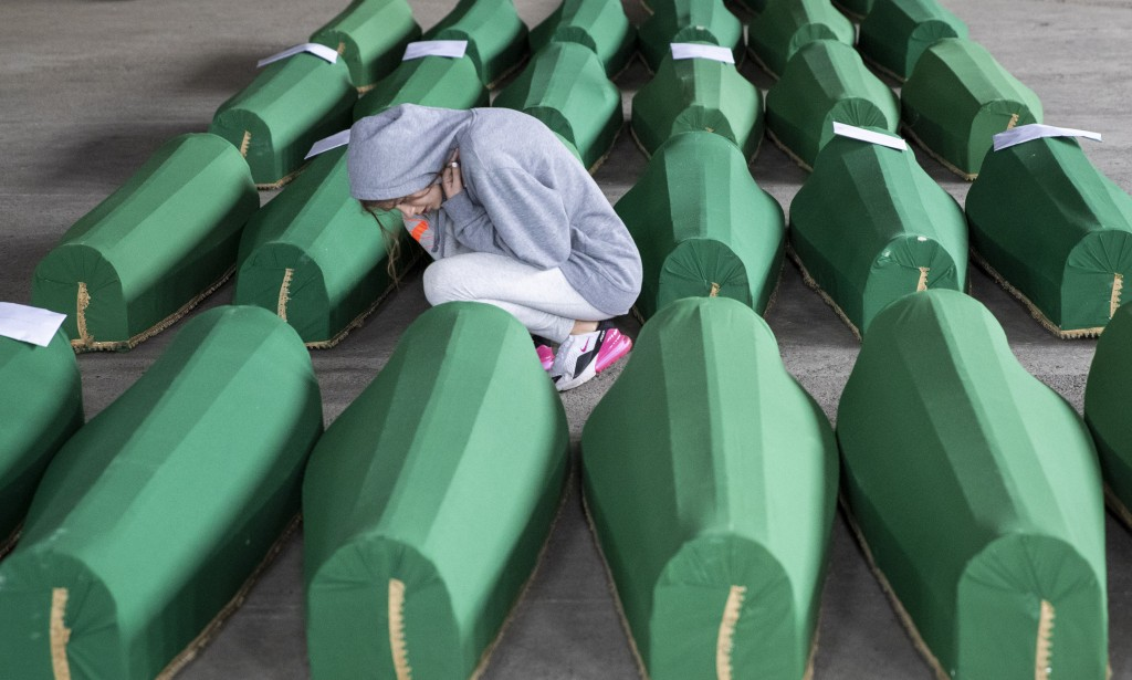 A girl inspects coffins prepared for burial, in Potocari near Srebrenica, Bosnia, Wednesday, July 10, 2019. The remains of 33 victims of Srebrenica ma...