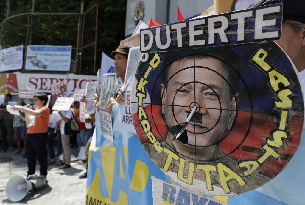 In this Wednesday, July 10, 2019, file photo, an image of Philippine President Rodrigo Duterte is shown inside a mock dartboard with slogans that read