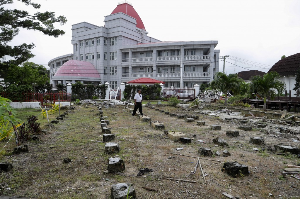 In this Wednesday, April 10, 2019, photo, a security guard walks amongst the ruins of the Tonga's historic Parliament House destroyed last year in Cyc