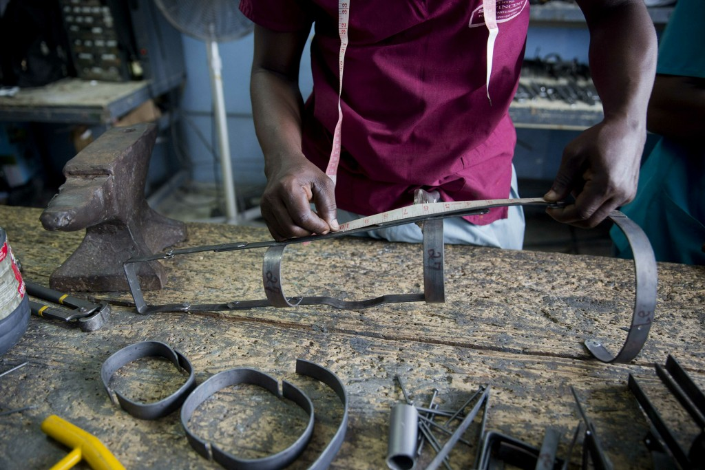 In this June 5, 2019 photo, technician Cereste Cherisme creates a lower limb orthotic steel brace at the workshop in the St. Vincent's Center in Port-