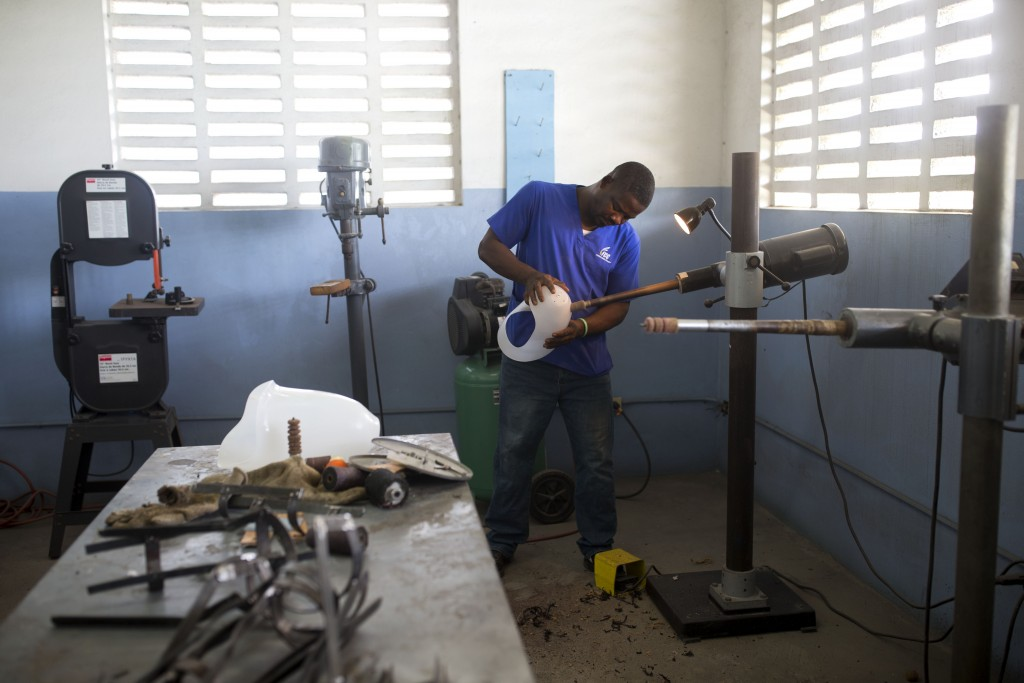 In this June 4, 2019 photo, former welder Wilfrid Macena works on a prosthetic socket in a workshop at St. Vincent's Center, in Port-au-Prince, Haiti....