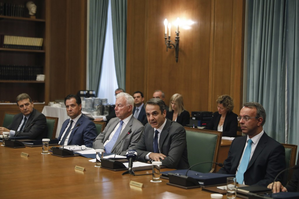 Greek Prime Ministers Kyriakos Mitsotakis, second right, speaks next to Finance Minister Christos Staikouras, right, as  the new government participat