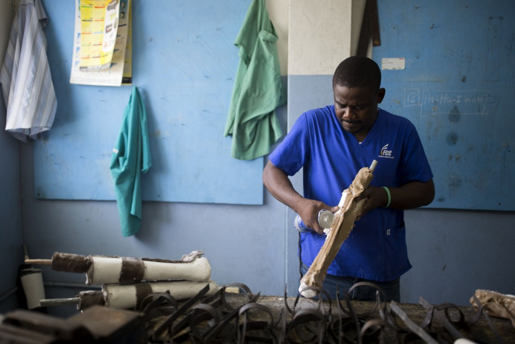 In this June 4, 2019 photo, prosthetic technician Wilfrid Macena works in a workshop at the St. Vincent's Center, an institution run by Haiti's Episco...