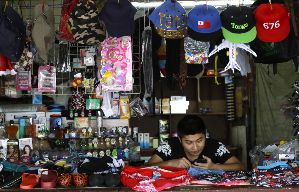 In this April 10, 2019, photo, a shopkeeper waits for business in Nuku'alofa, Tonga. China is pouring billions of dollars in aid and low-interest loan