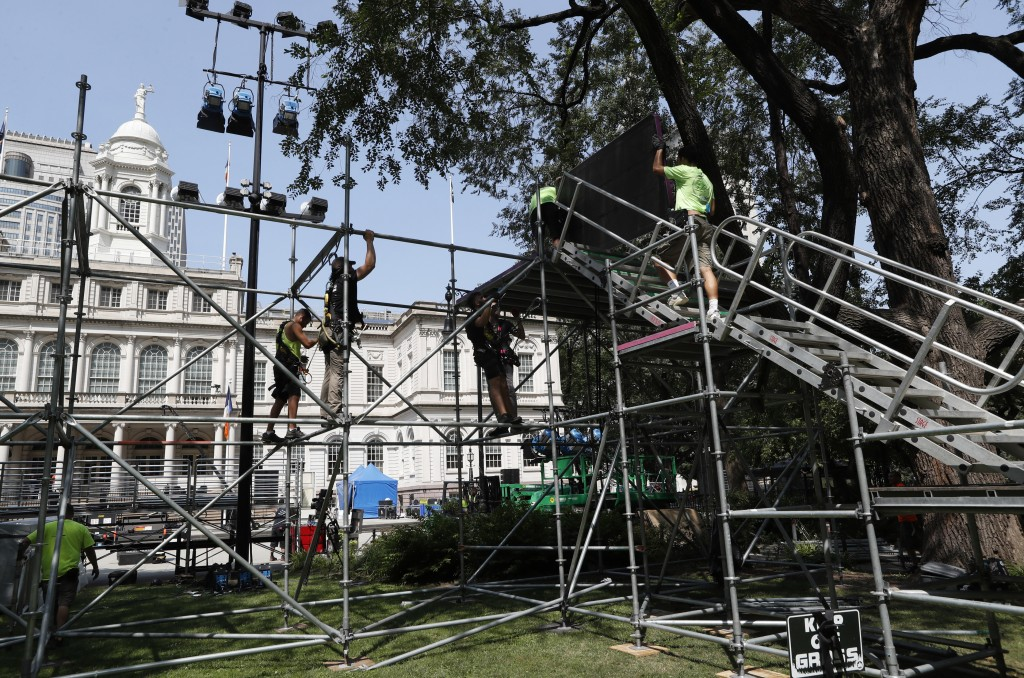 Workers construct a high platform for media one day ahead of a City Hall ceremony that will follow a ticker-tape parade for the U.S. Women's soccer te