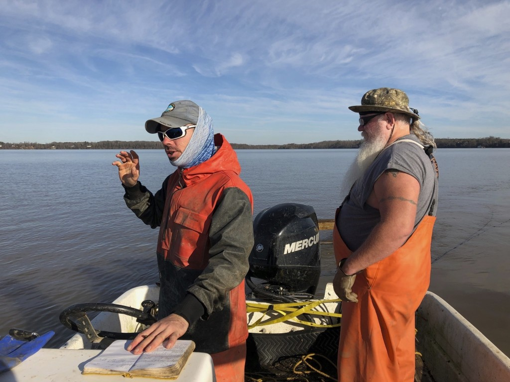 In this Saturday Dec. 29, 2018 photo, Matthew Balazik, a sturgeon research ecologist with Virginia Commonwealth University and the U.S. Army Corps of