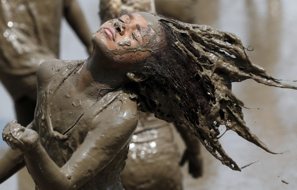 Jaylee Fogg, 10, throws back her mud crusted hair during Mud Day at the Nankin Mills Park, Tuesday, July 9, 2019, in Westland, Mich. The annual day is