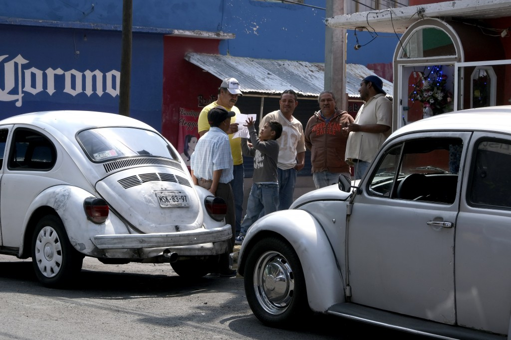 "Taxi drivers gather around their Volkswagen Beetles in a neighborhood of Mexico City known colloquially as ""Vocholandia,"" for its love of the classic"