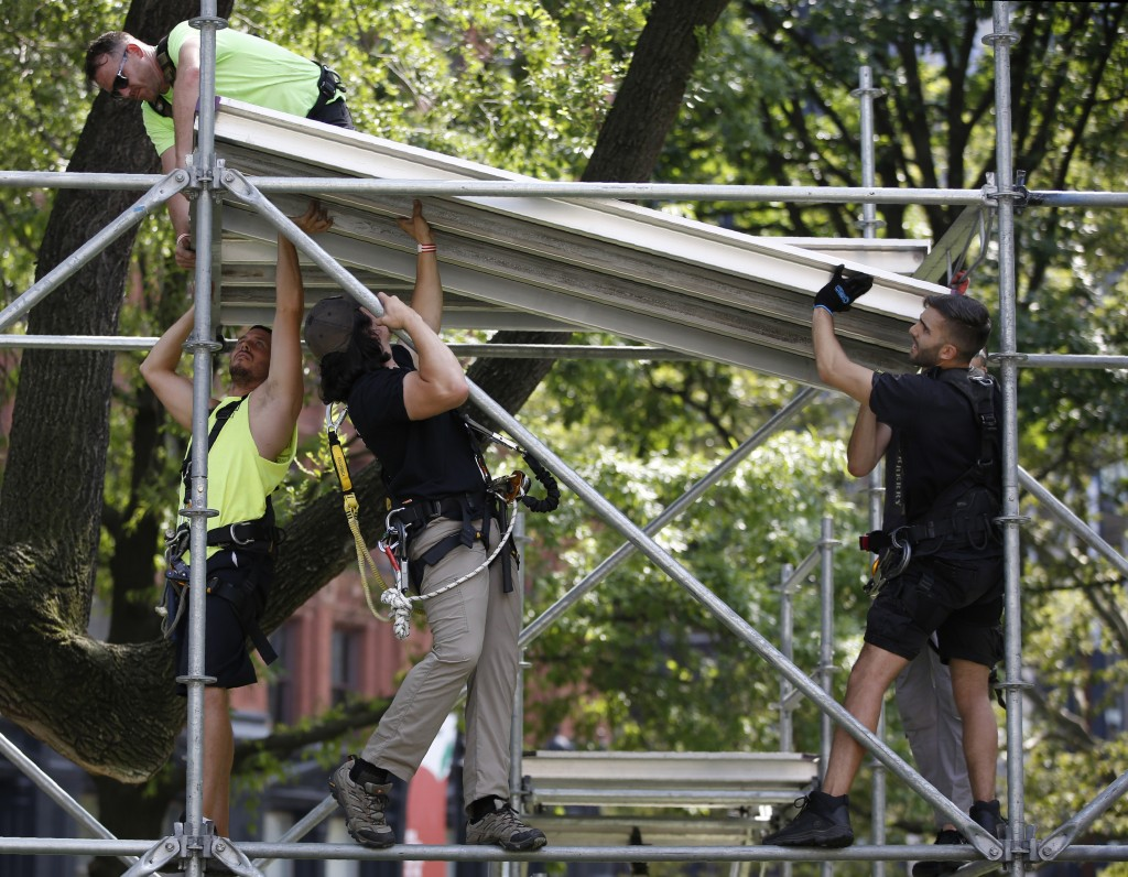 Workers assemble a press platform at City Hall one day ahead of a ticker-tape parade and ceremony honoring the four-time World Cup winning U.S. women'