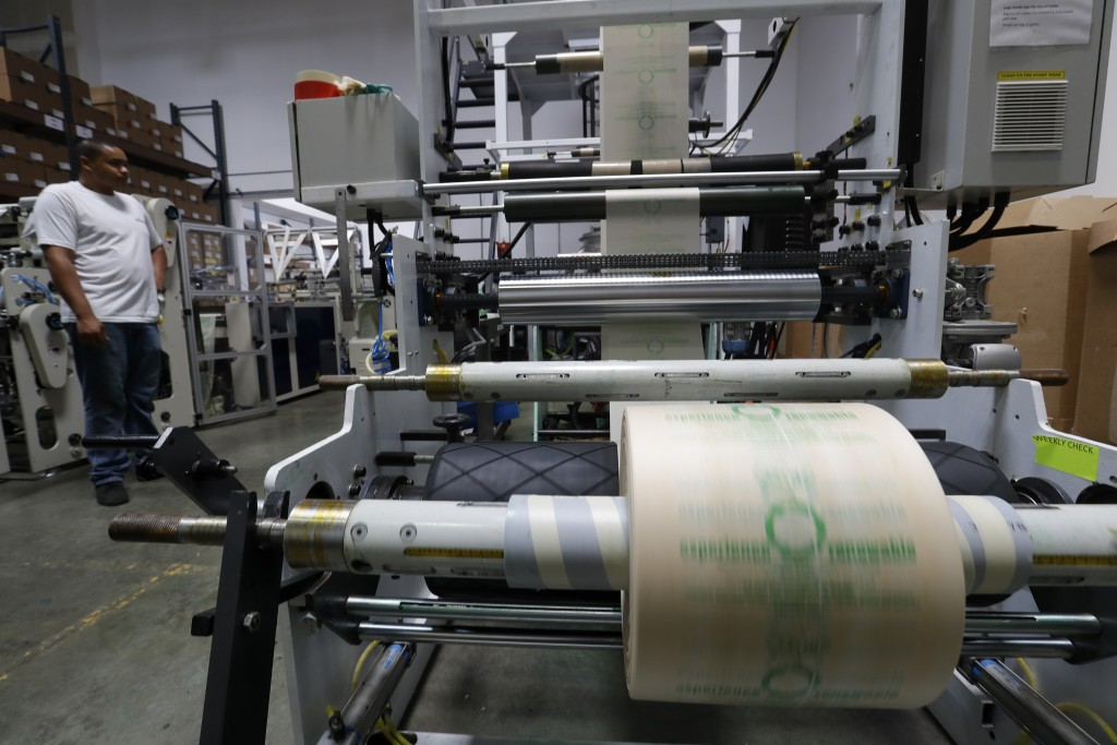 In this Friday, July 5, 2019, photo Andre Harris works on the line at beyond Green, a maker of biodegradable bags in Lake Forest, Calif. (AP Photo/Chr...