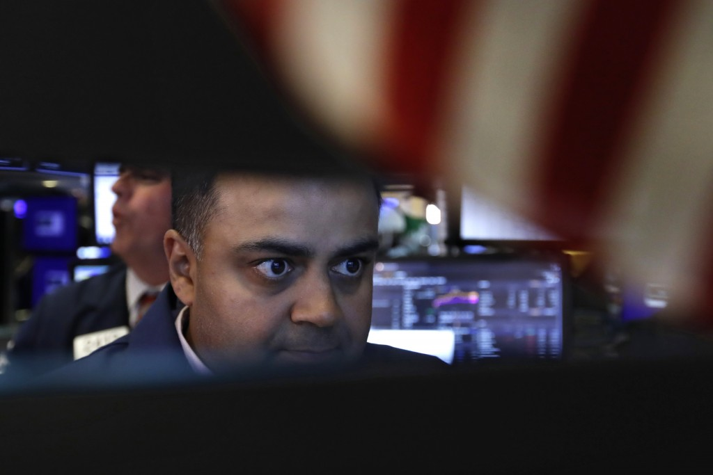 FILE - In this June 18, 2019, file photo specialist Dilip Patel works at his post on the floor of the New York Stock Exchange. The U.S. stock market o...