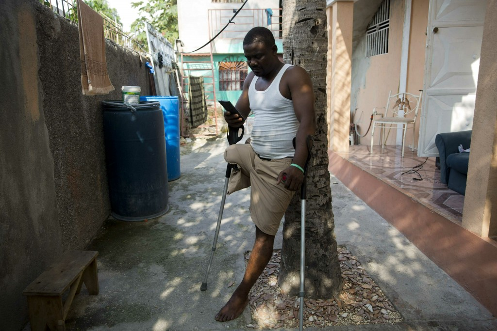 In this June 5, 2019 photo, amputee and prosthetic technician Wilfrid Macena leans against a tree in his yard as he looks at his smart phone, in Carre