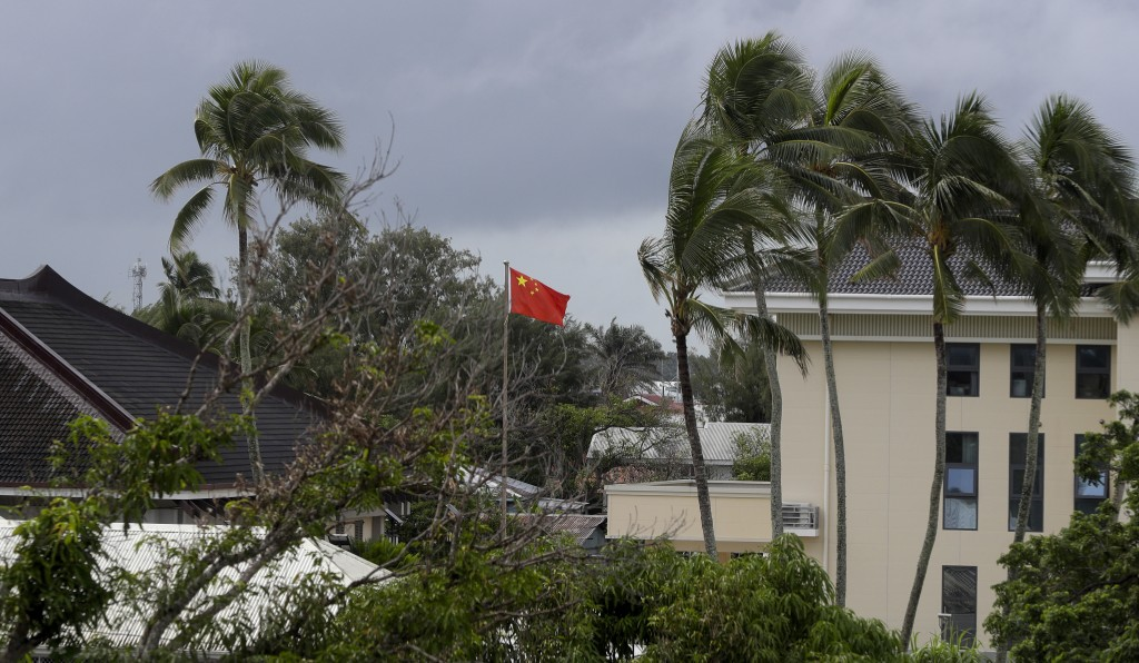 In this April 8, 2019, photo, a Chinese flag flies outside the Chinese Embassy in Nuku'alofa, Tonga. China is pouring billions of dollars in aid and l
