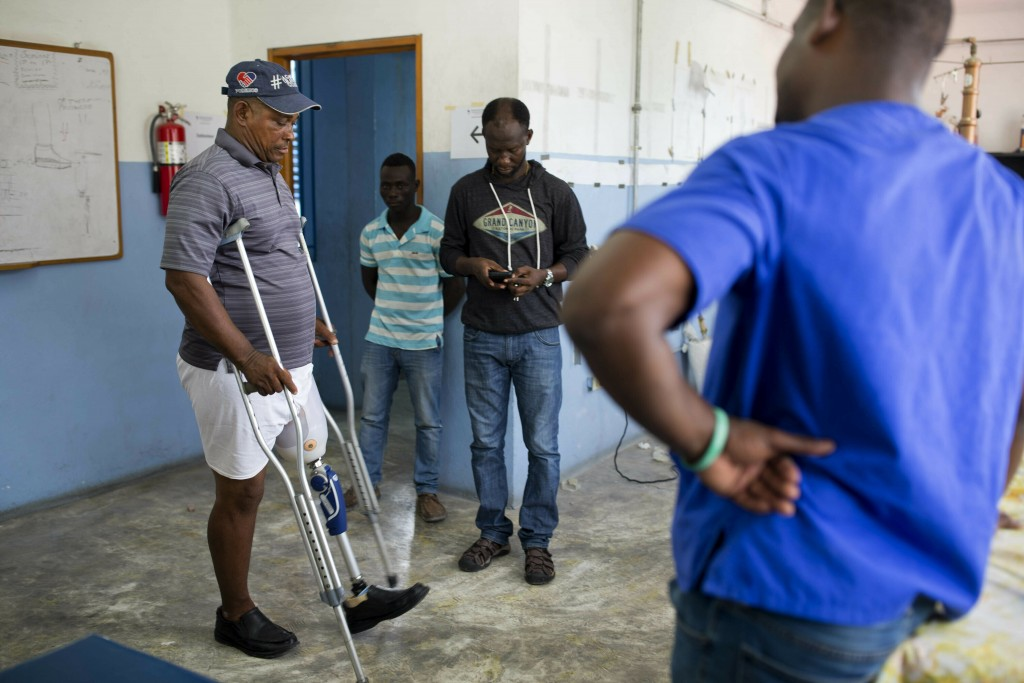 In this June 4, 2019 photo, amputee Salomon Labossiere learns how to walk with his new prosthetic leg as Wilfrid Macena offers encouragement, at the S...