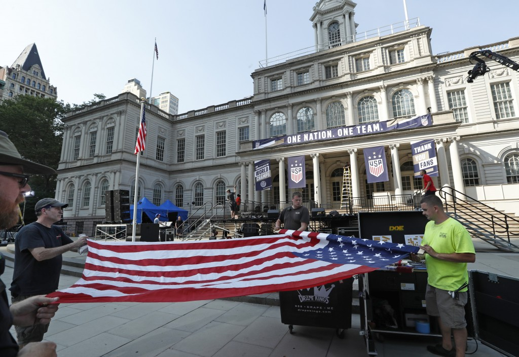 Workers unfurl a flag as they prepare New York City Hall one day ahead of Wednesday's ticker-tape parade and ceremony for the U.S. Women's four-time W