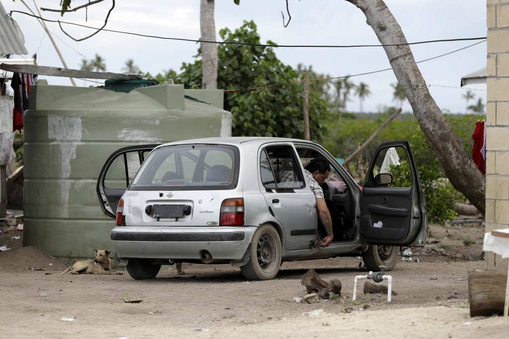 In this Sunday, April 7, 2019, photo, a man prepares to drive his car in Nuku'alofa, Tonga. China is pouring billions of dollars in aid and low-intere