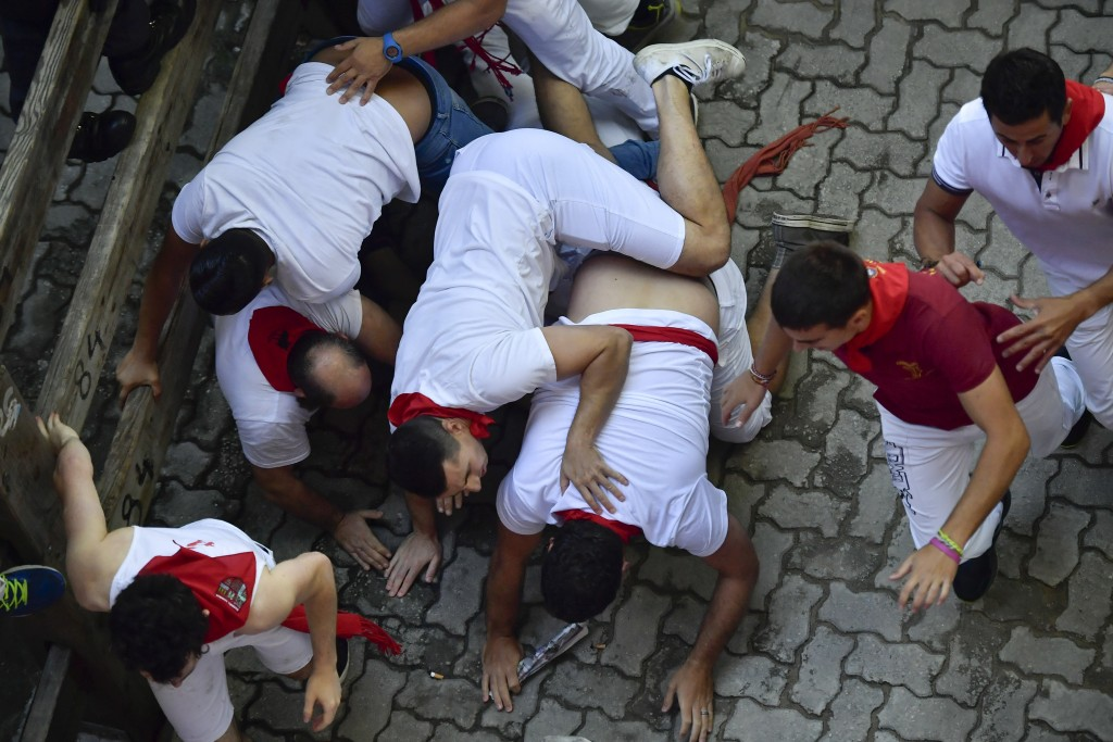Revellers fall down during the running of the bulls at the San Fermin Festival, in Pamplona, northern Spain, Wednesday, July 10, 2019. Revellers from