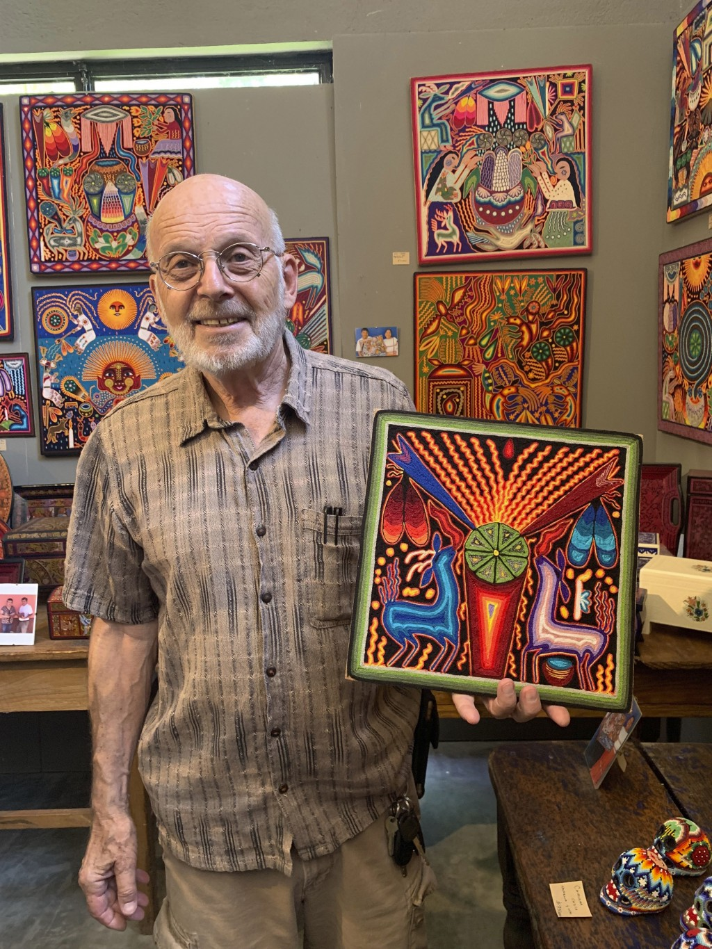 This June 17, 2019 photo shows gallery owner Mayer Shacter holding a Huichol yarn painting, at Galeria Atotonilco near San Miguel de Allende, Mexico.