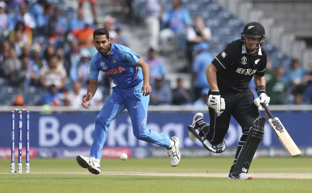 India's Bhuvneshwar Kumar, left, runs to field the ball after a shot played by New Zealand's Tom Latham during the Cricket World Cup semi-final match ...