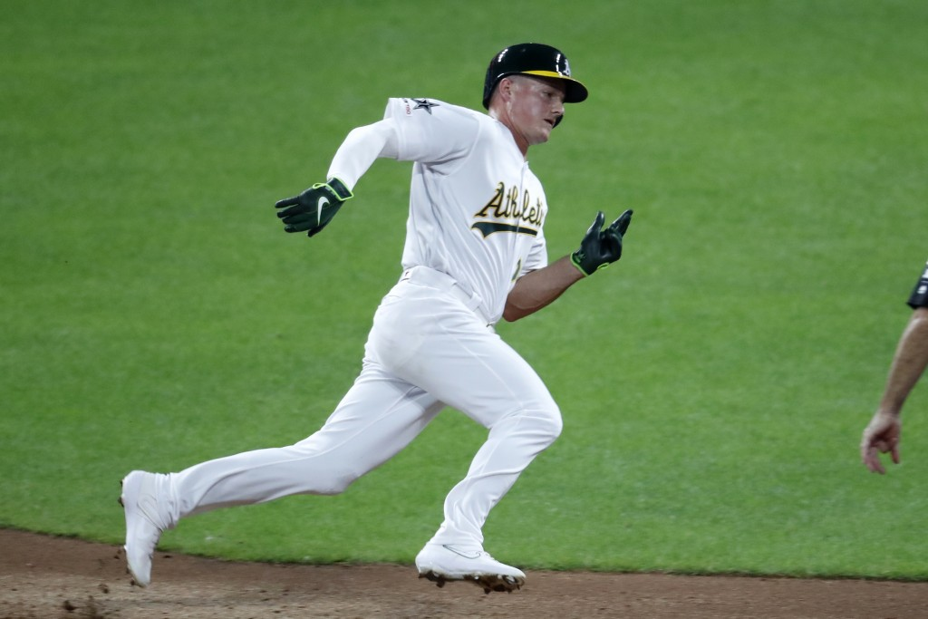 American League Matt Chapman, of the Oakland Athletics, rounds to second on his way to third on a single by American League teammate James McCann, of