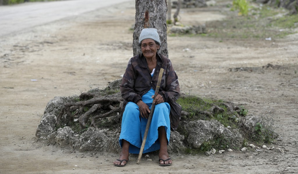 In this April 7, 2019, photo, a local woman sits under a tree in Nuku'alofa, Tonga. China is pouring billions of dollars in aid and low-interest loans