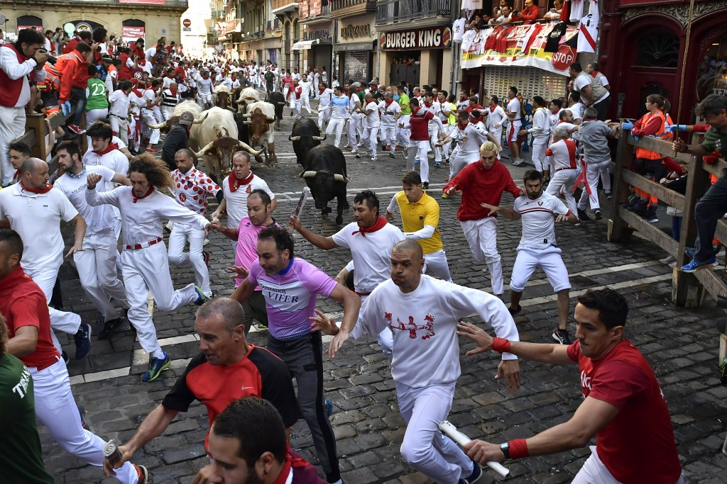 Revellers run next to fighting bulls during the running of the bulls at the San Fermin Festival, in Pamplona, northern Spain, Thursday, July, 11, 2019...