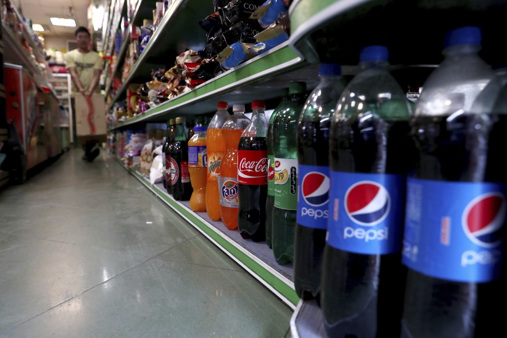 Bottles of Pepsi and Coca-Cola are displayed in a grocery store in downtown Tehran, Iran, Wednesday, July 10, 2019. Whether at upscale restaurants or